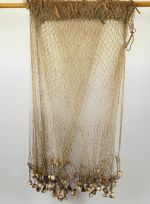 Large fishing net of whitish parau with numerous weights of white coral tied with strands of plaited coconut fibre along the lower long sides, and floats of small parau sticks along the upper long sides.