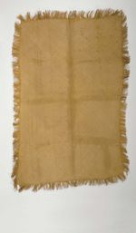 A piece of very fine matting with a fringed border made of light brown plantain leaf fibres.