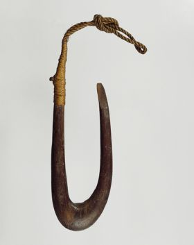 Fishhook made of a finely polished piece of hardwood. The point of the hook is flat on the side and the upper end of the shank is supported and secured with plaited coconut fibres.