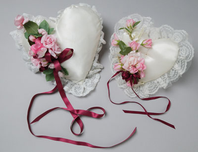 Two love-heart shaped cushions, similar in appearance, decorated with maroon ribbons and pink flowers.