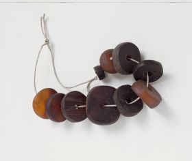 Jewellery & Adornment made from reddish-brown and blackish-brown tortoise shell discs arranged on a string.