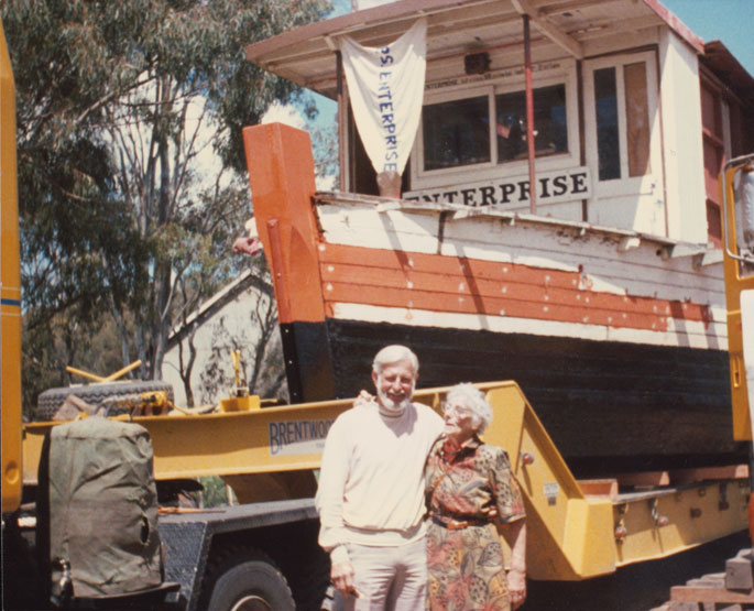 A colour photograph of John Robinson and his sister with the PS Enterprise in the background.