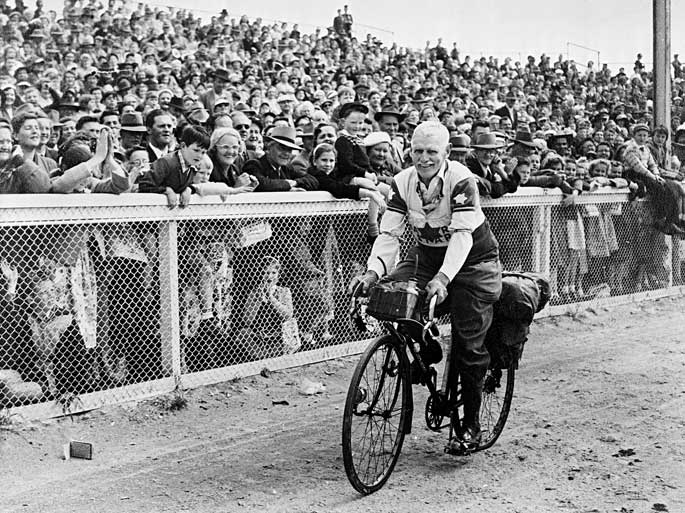 A black and white photograph of Ernie Old, aged 73, finishing his 4000-kilometre ride to Brisbane and back at the showgrounds, Melbourne, 1947.