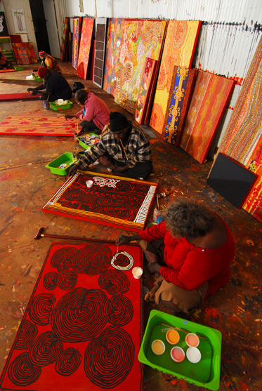 Colour photograph showing five seated Aboriginal artists working on individual paintings. Various other paintings line the rear wall.