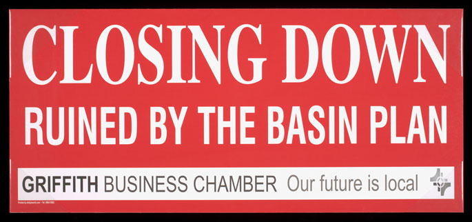 Colour photograph of a sign, printed in white on a red background, which reads: 'CLOSING DOWN, RUINED BY THE BASIN PLAN. Griffith Business Chamber. Our future is local'.