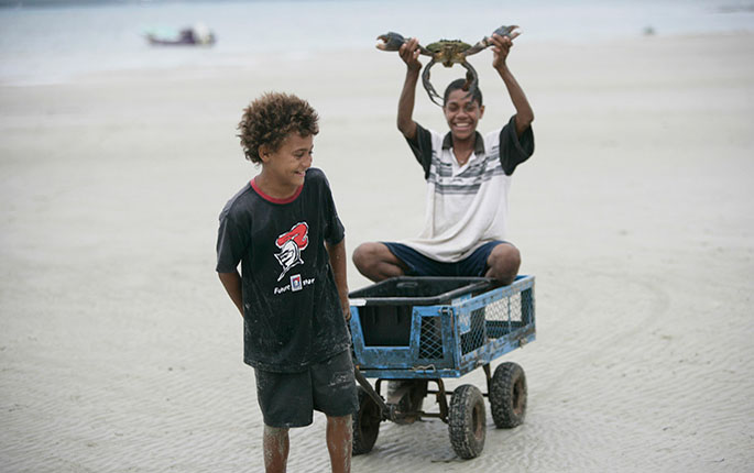 Two boys catching crabs on a beach.