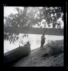 A black and white photographic negative that depicts an adult standing on a riverbank next to a canoe.