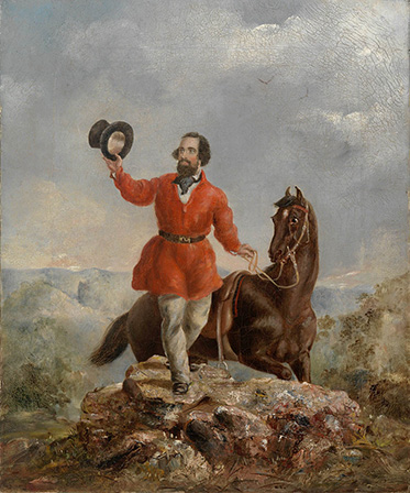 A bearded man wearing a bright red jacket and holding his top aloft stands on a rocky outcrop holding the reins of his horse.