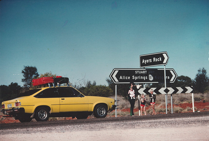 Lindy Chamberlain holding Azaria Chamberlain, with Aidan and Reagan Chamberlain, standing on Stuart Highway with sign to 'Ayers Rock', alongside their Torana, 16 August, 1980.