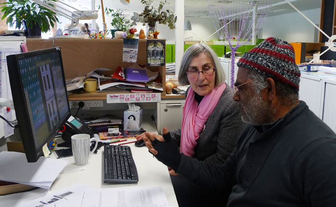 A man and woman discussing the contents of a computer screen