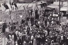 A crowd of people making their way through the sideshow alley at the Royal Adelaide Show.
