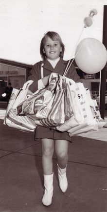 Black and white photograph of a young girl carrying multiple sample bags and a balloon and small doll on sticks.