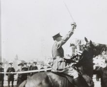 Black and white photo of a man on horseback with sword raised as he approaches a ribbon.