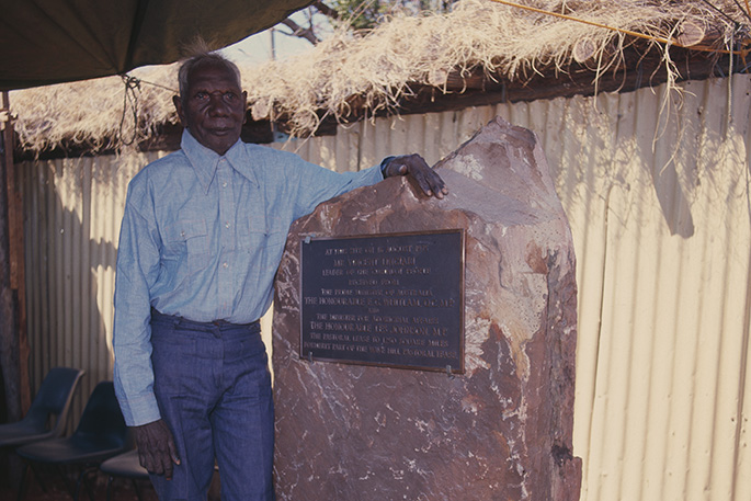 Aboriginal man standing next a plaque set into a large piece of rock