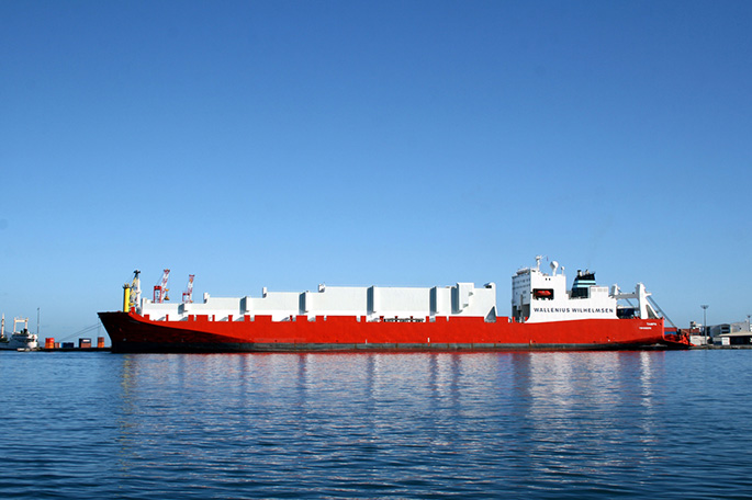 Red and white container vessel moored.