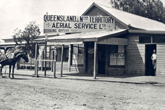 Timber shopfront with large sign on roof reading Queensland & Northern Territory Aerial Service Ltd Booking office. The road is unsealed and a horse in harness is visible at left. A man is standing is a doorway looking at the camera.