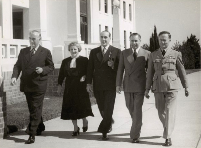 Four men and a woman walking abreast along the front of Old Parliament House.
