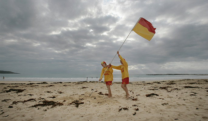 Two young people plant a lifesaving flag in almost deserted beach