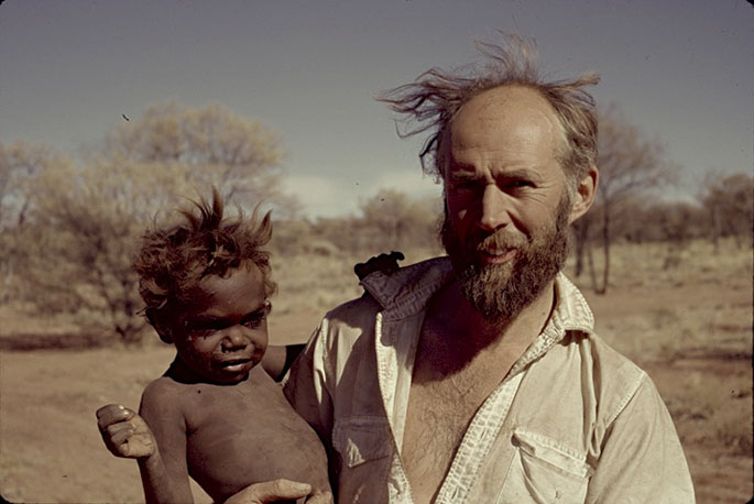 A man in a desert holding a young Aboriginal boy.