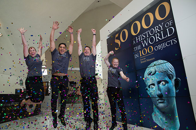 four people jumping for joy alongside a large sign which says '50000 A HISTORY OF THE WORLD IN 100 OBJECTS from the British Museum. A blue-ish grey coloured statue's head is portrayed in the right hand bottom corner. Confetti is being thrown at them.