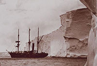 A sepia photo of a ship sailing among icebergs