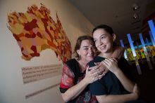Two women standing in front of a map of Australia on the wall.
