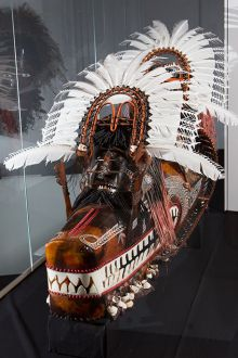 Large cultural mask with brown and yellow ochre tones, feathers and other materials.