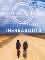 Two people cycling on a dirt road leading across a vast plain