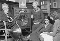 Black and white photo of a man and three women listening to a radio