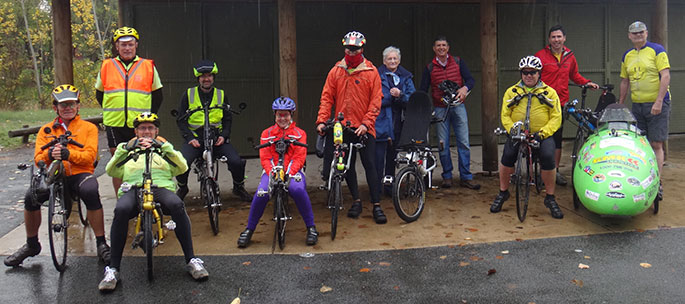 Group of people with bicycles, standing under and in front of outdoor cover