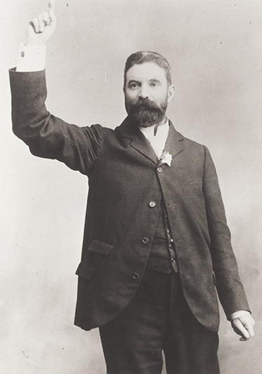 studio photo of man with dark beard posing as though he is addressing a crowd