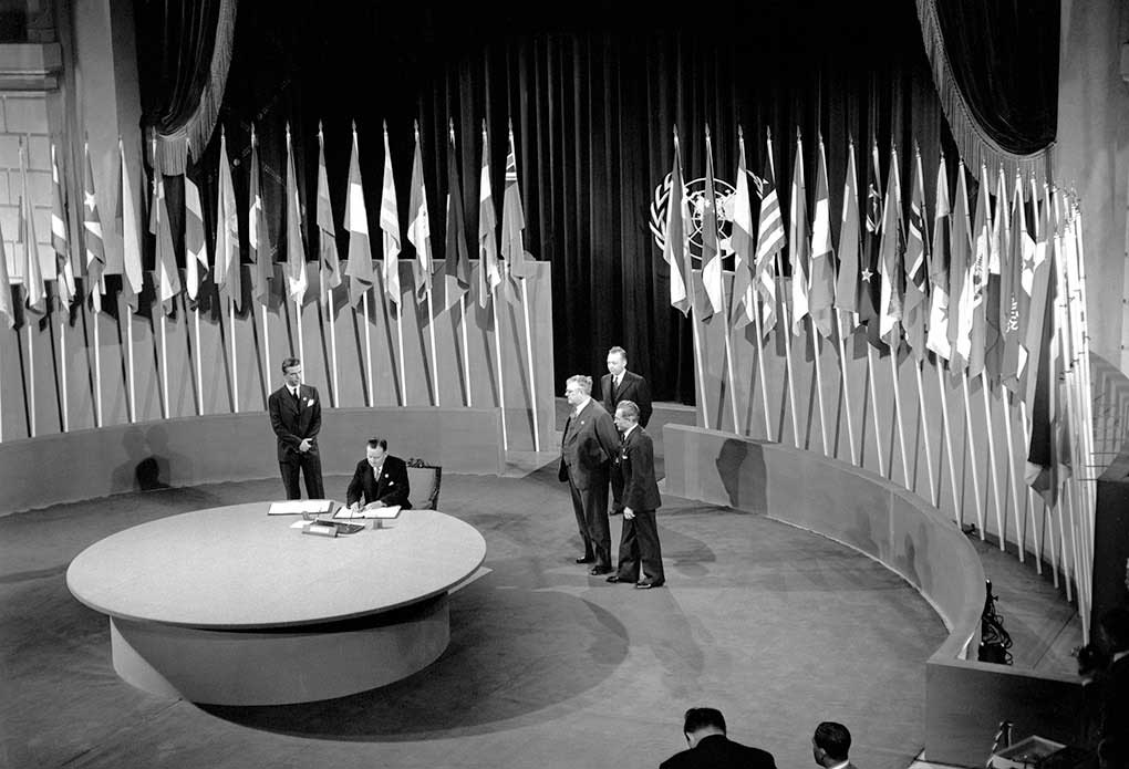 Interior black and white photo of man sitting at large round table signing a document, with four men standing behind him and a series of flags arranged behind them.