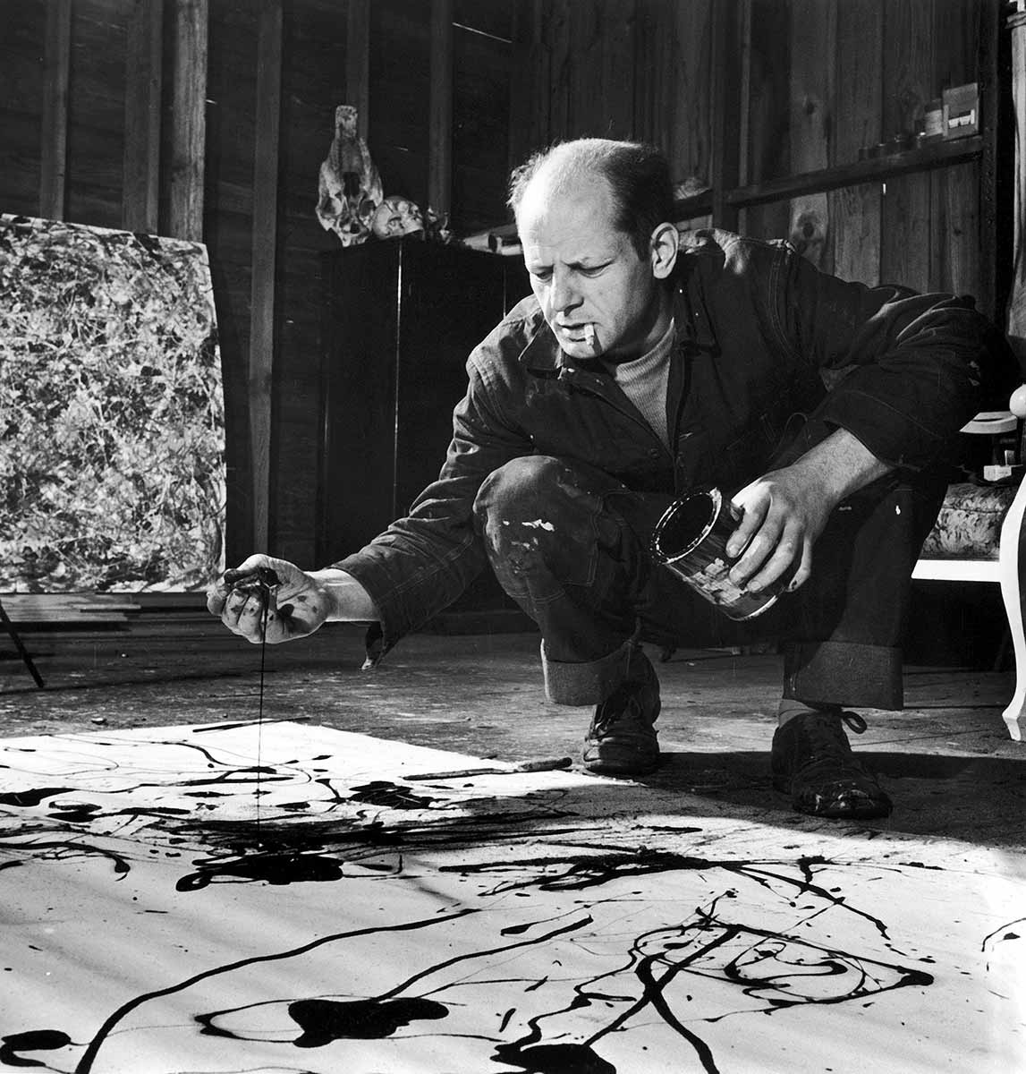 Black and white photo of balding, middle-aged man crouches by canvas spread on the floor. He has a cigarette in his mouth, a paint can in one hand. His other hand seems to be covered in paint. He is frowning intently at the canvas, which has a few splotches of dark paint on it. - click to view larger image