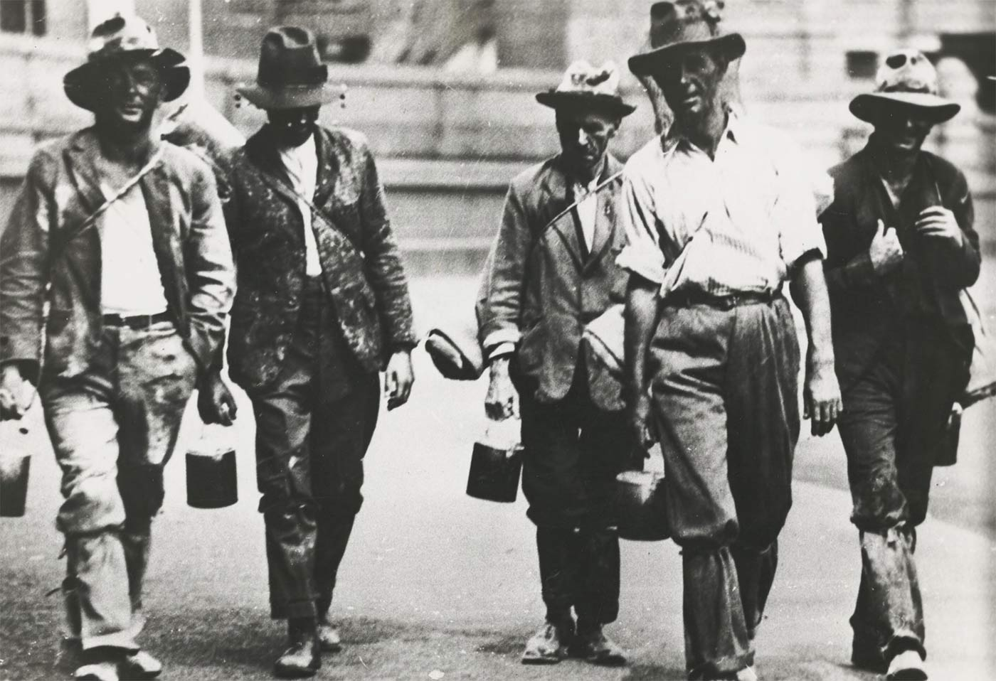 Five men walking towards the camera dressed in shabby clothes. Most are carrying swags and bill cans