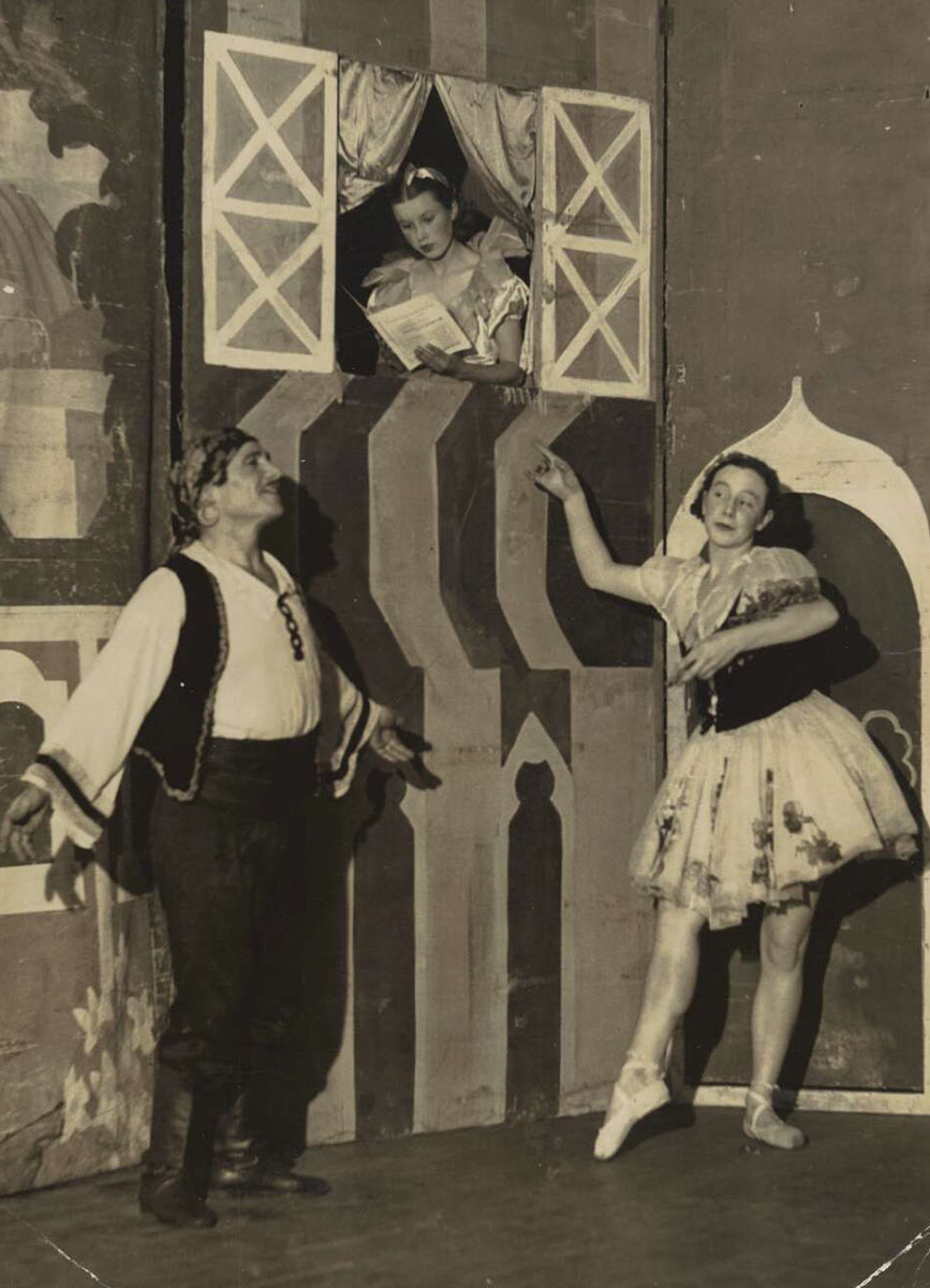 Three performers on stage. Two of them, a man and a woman in traditional folk costume, strike balletic poses while another performer reads a book in a window above their heads. - click to view larger image