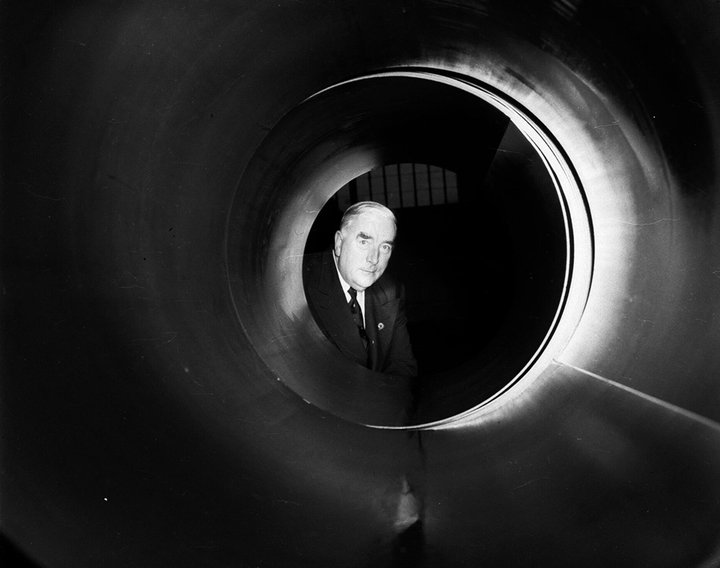 a black and white photo of an older man looking through a tunnel