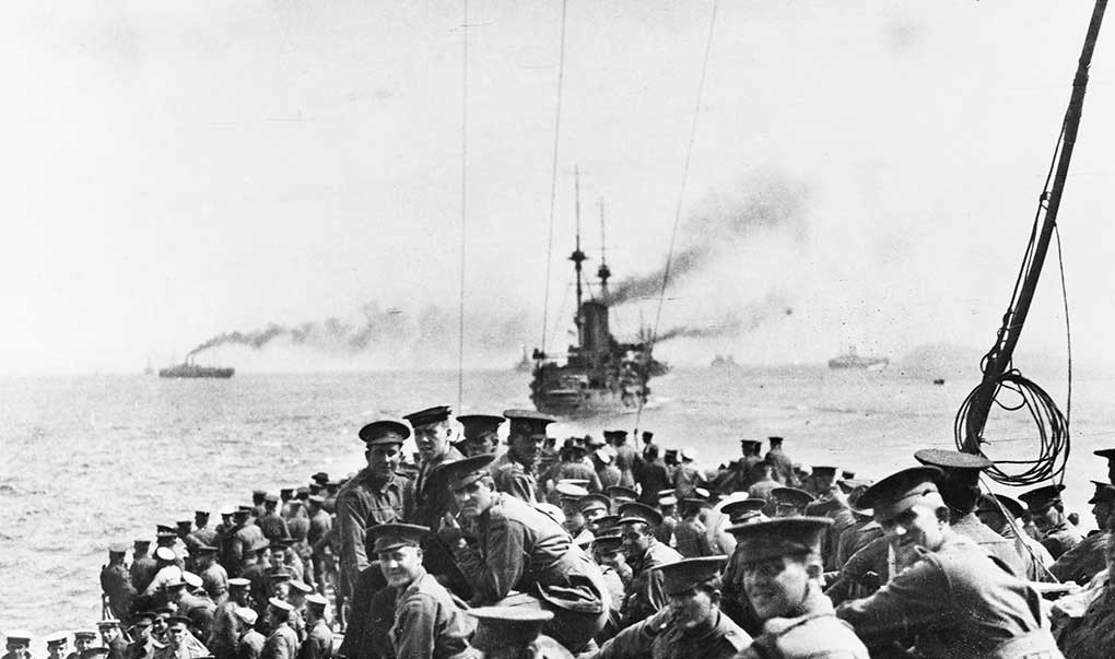 Grainy black and white photo taken on board a boat full of Australian soldiers, with ships in background.
