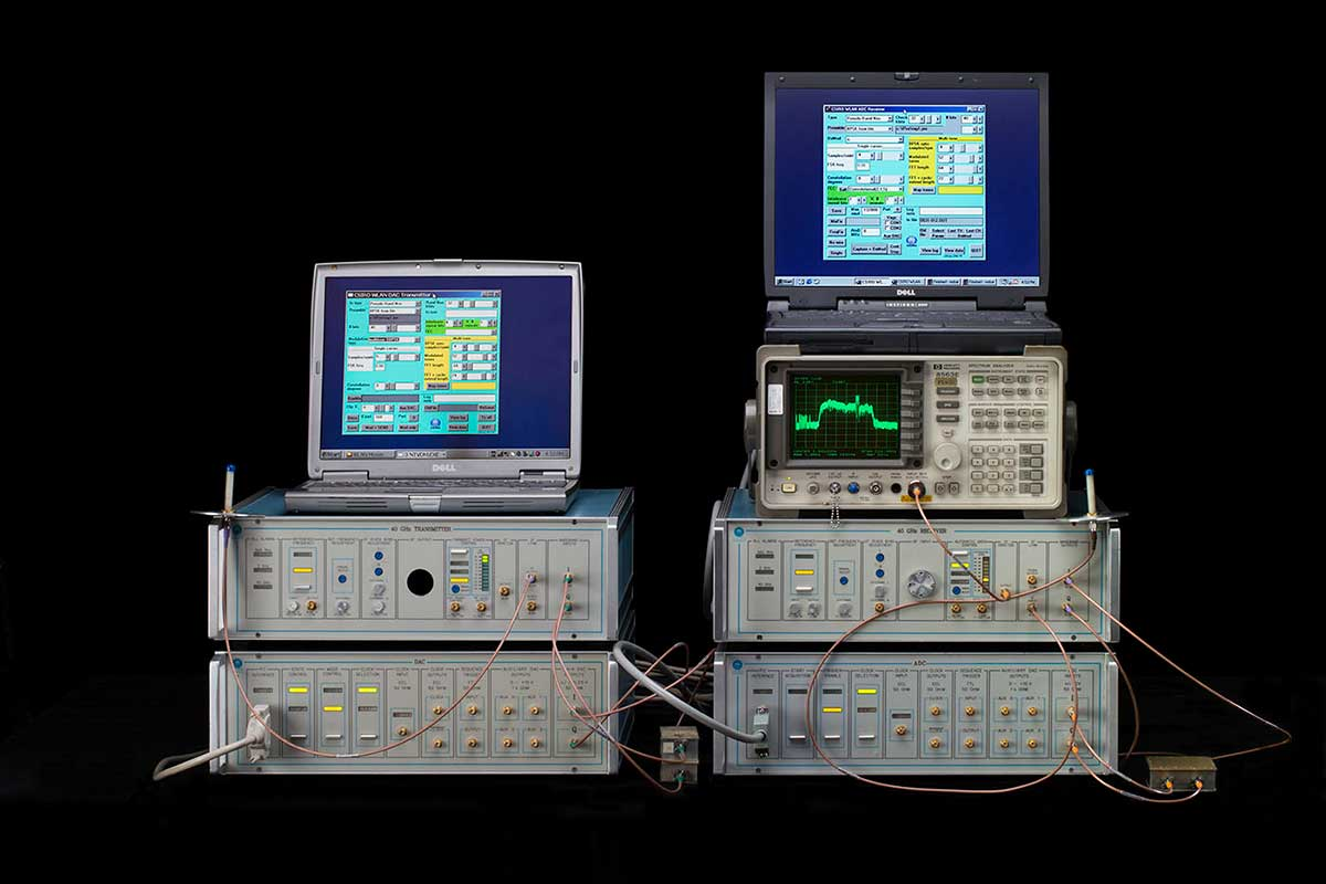 Computer set-up with four grey hardware boxes in two stacks topped by two notebook computers showing data and a spectrum analyser on the right.