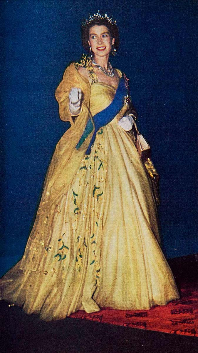Queen Elizabeth II wearing a floor-length pale-yellow gown, crown, white gloves and blue ceremonal sash. The image shows the queen standing on a red printed carpet, with a deep blue backdrop.