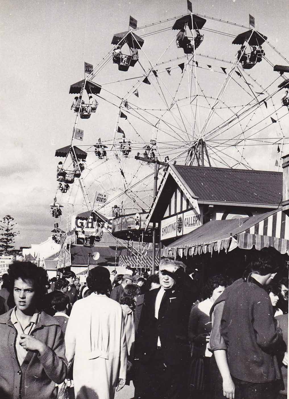 Black and white photo showing a ferris wheel in the distance and a group of people walking down sideshow alley in the foreground. - click to view larger image