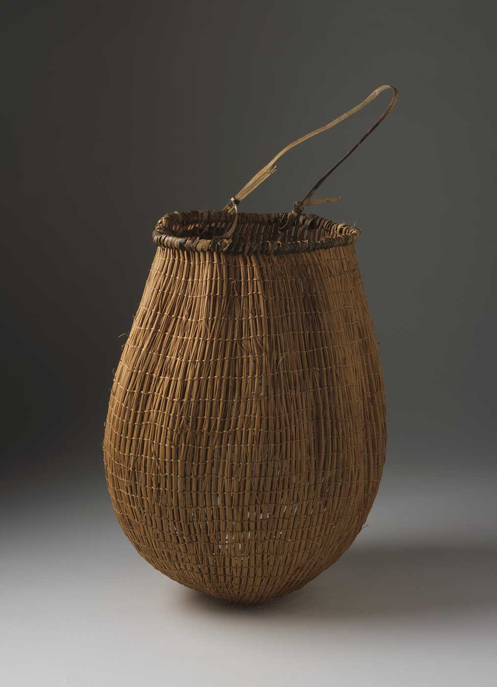 Colour photograph of a basket with handle at top and conical-shaped base. - click to view larger image