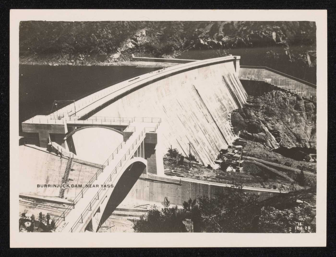Black and white photograph showing a dam and dam wall. - click to view larger image