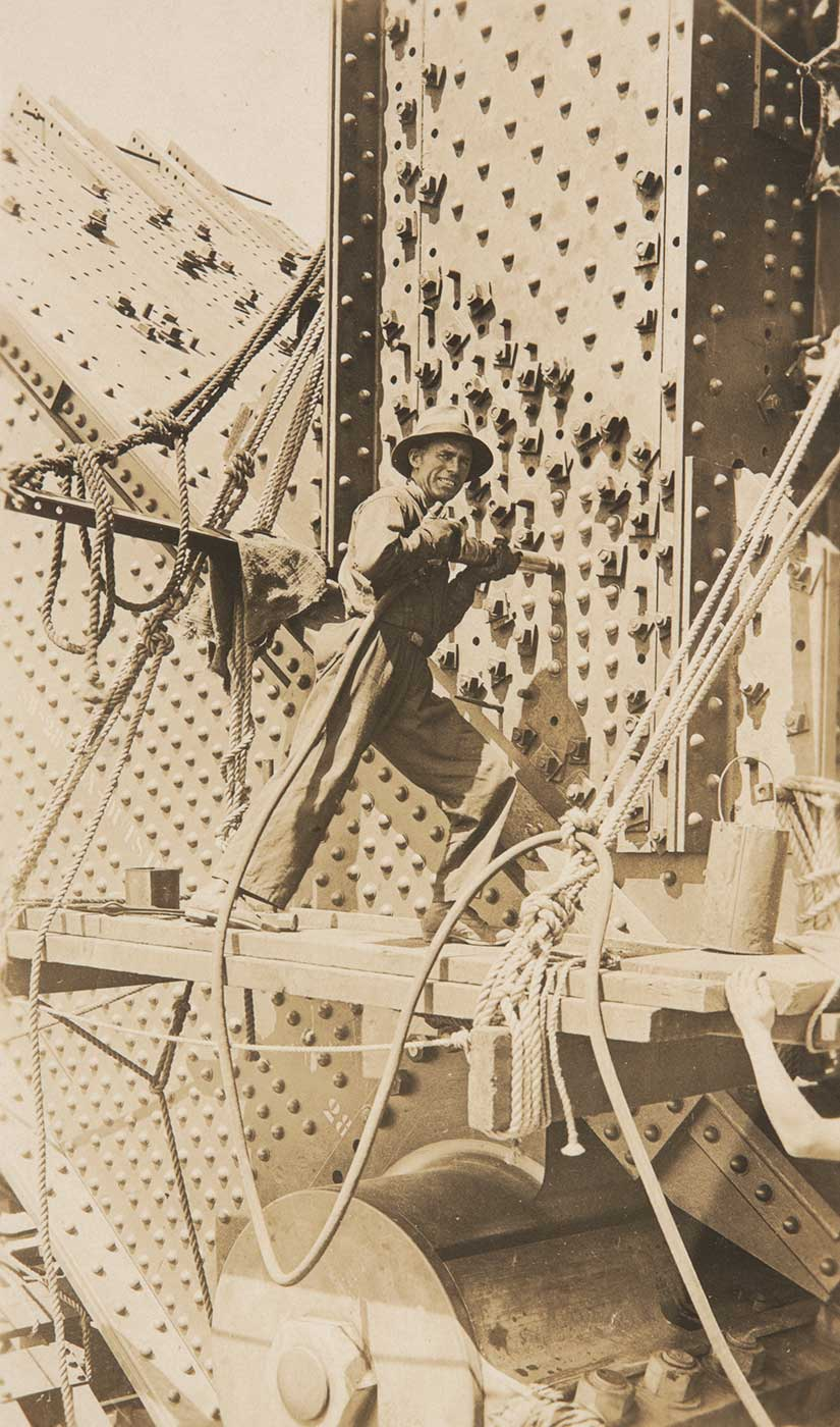 A man using a hand-held rivet gun during the construction of the Sydney Harbour Bridge. - click to view larger image