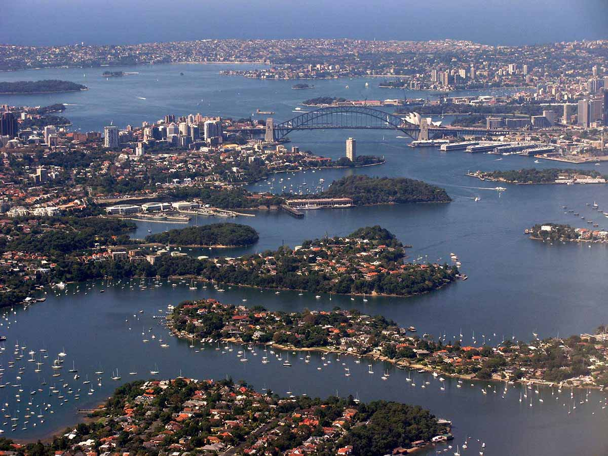 An aerial view of Sydney Harbour with the bridge and opera house at centre. Many small boats are moored in the foreground. - click to view larger image