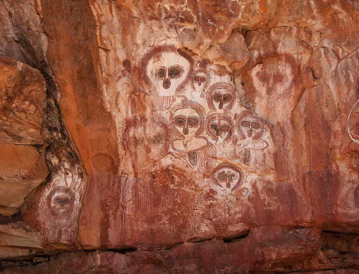 Colour photograph showing Aboriginal art on a rock wall. Numerous faces with oversized eyes and no mouth are depicted on the rock, in shades of yellow, red, black and white. - click to view larger image