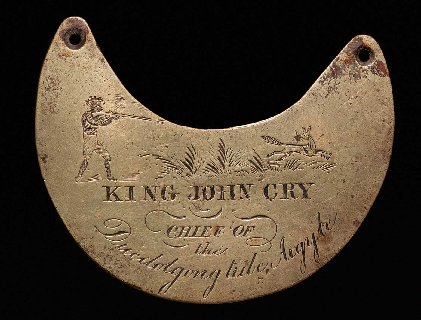 A crescent shaped, brass breastplate with a hole at the edge of each horn to attach a chain. 'KING JOHN CRY / CHIEF OF / the / Duedolgong Tribe, Argyle' is engraved on the anterior surface. A man with a rifle is engraved on the left horn, and a fox is engraved on the right horn - click to view larger image