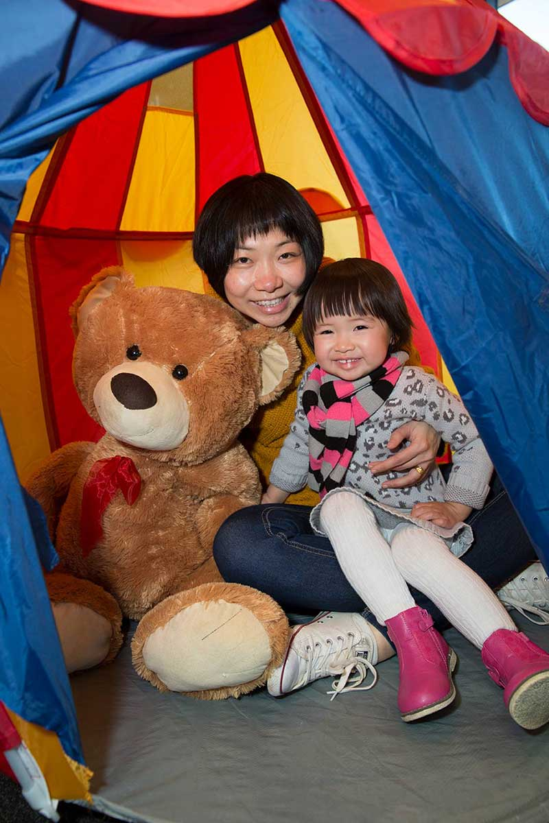 A woman is sitting inside a colourful tent, holding a large brown teddy bear under one arm and a young girl under the other.