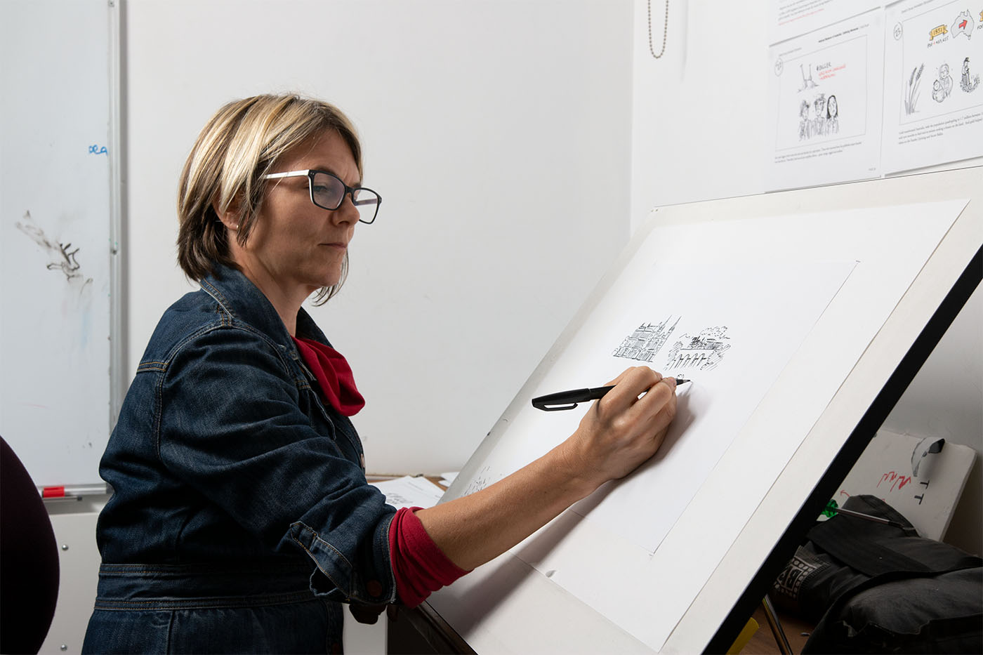 Side view of a woman seated before a large easel, sketching a cityscape on white paper in black pen. - click to view larger image