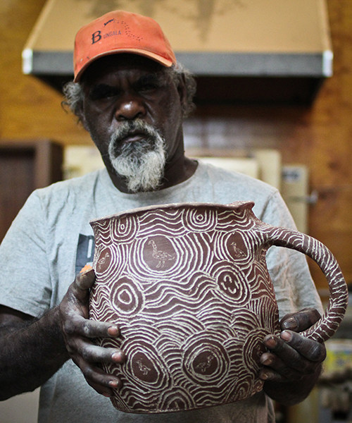 Man holding a patterned vessel - click to view larger image