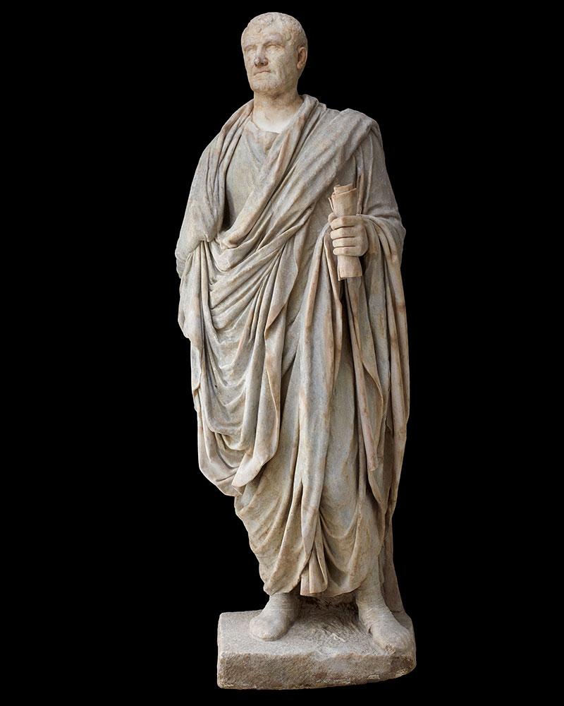 A marble statue of a Roman man wearing robes and holding a scroll in his left hand. - click to view larger image
